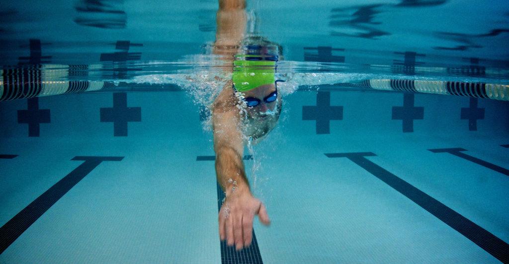 Мужчина плывет под водой кролем