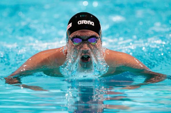 Мужчина плывет брассом в бассейне